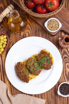 Мясные котлеты с картофельными специями, зеленью, помидорами, вид сверху