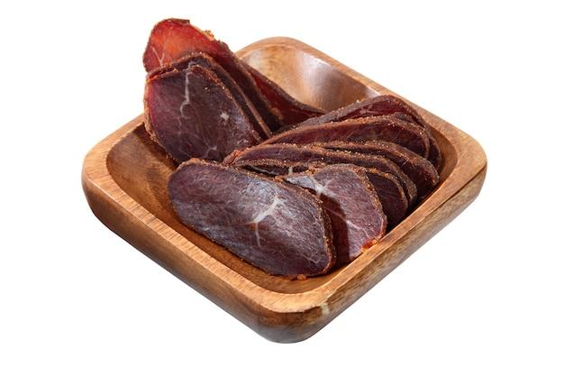 肉の可憐なバストゥルマ、スパイスを加えた乾燥牛肉の切り身、薄くスライスしたものを木製のボウルに入れ、白い背景で隔離します。