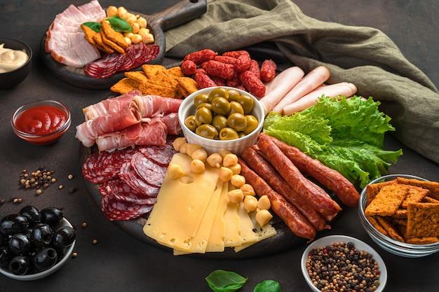 Мясные деликатесы различных видов, сыры, салат, оливки и соус на деревянной доске на коричневом фоне.