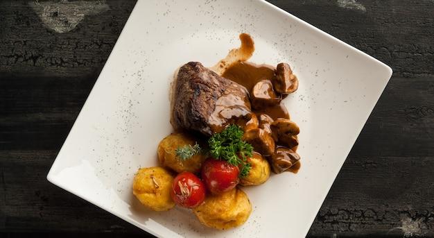 木製の古い表面の肉料理。木製の古いボード上の白いプレートにジャガイモと揚げ肉