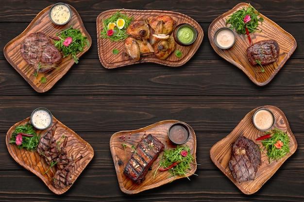 Мясные блюда, стейк из куриных ребрышек на деревянном фоне с местом для текста