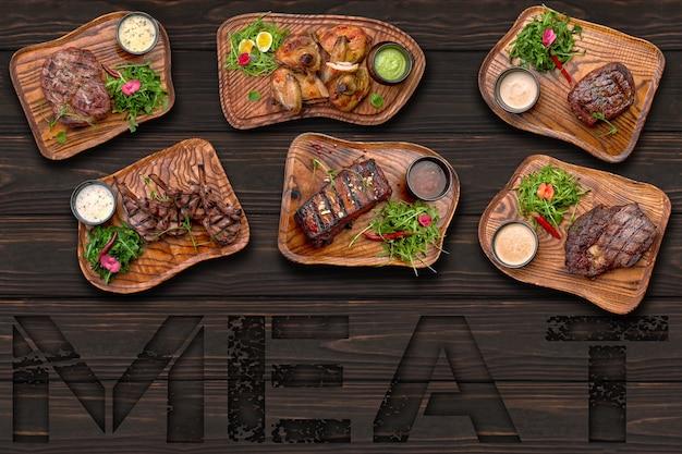 Мясные блюда стейк из куриных ребрышек на деревянном фоне с надписью мясо