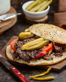 Meat doner with marinated pickels and tomato in bread.