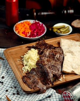 Meat doner with rice and lavash on wooden board