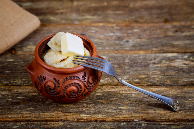 Meat dumplings pelmeni with sour cream on rustic background