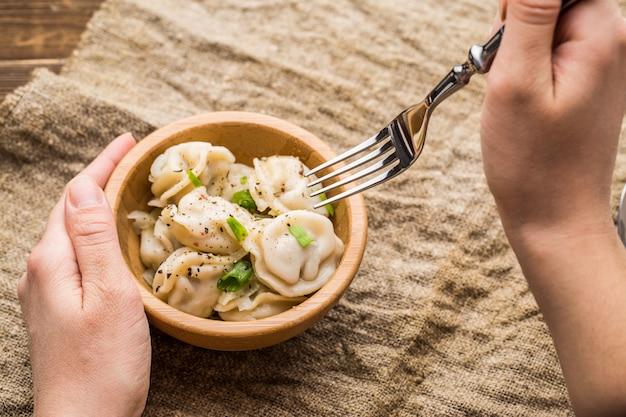 Meat dumplings - russian pelmeni, ravioli with meat on a wooden plate