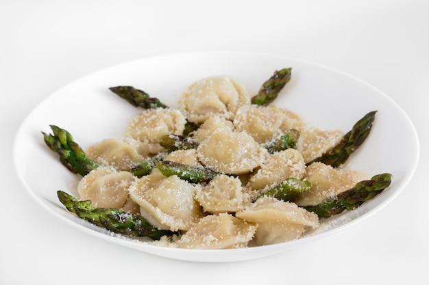Meat dumplings with parmigiano and asparagus on white plate.