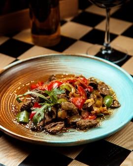 Мясо фахитас с жареным луком зеленым перцем и кунжутом на тарелке