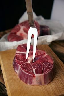 Вилка для мяса в стейке из ангуса. крупный план на деревянном столе перед несосредоточенными стейками.