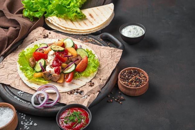 Мясо, жареный картофель, овощи, салат и соус на тонкой питте на коричневой разделочной доске. приготовление тако, шаурмы, буррито. вид сбоку, копия пространства.
