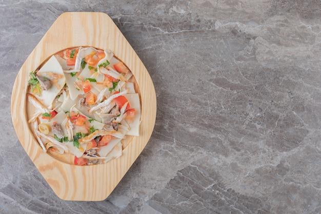 Мясо, зелень, помидоры и макароны на деревянной тарелке, на мраморе.