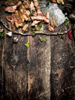 Мясной гриль. нарезанная свинина на гриле со старым топориком, специями и зеленью. на старом деревянном столе.
