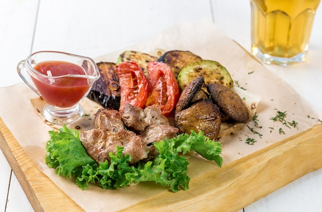 Meat and grilled vegetables with greens and sauce on a wooden board