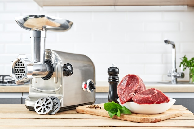 Meat grinder with fresh meat on wooden table in kitchen interior