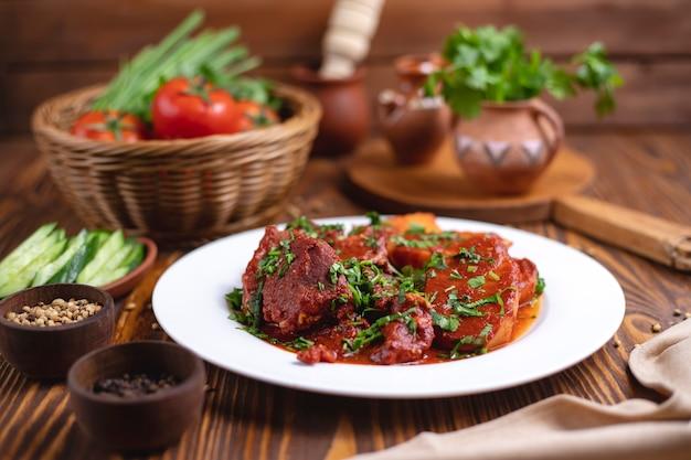 Мясо в томатном соусе с картофелем, зеленью и огурцом