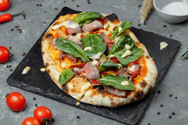 Мясная итальянская пицца с ростбифом, кусочками стейка, плавленым сыром, с оливками и сыром чеддер. закройте, макрос. концепция время пиццы.