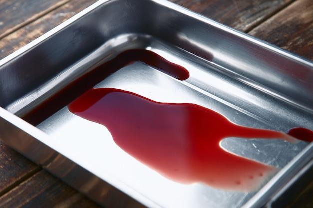 Succo di carne, sangue in una pentola d'acciaio di metallo, primo piano