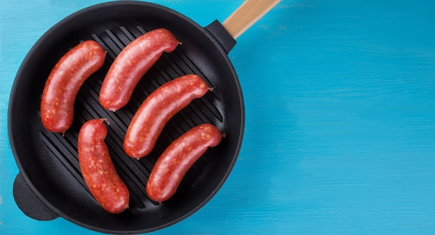Meat juicy sausages in frying pan on blue background