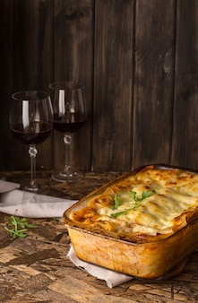 Meat lasagna. red wine in wineglass. homemade italian lasagna with bolognese and bechamel