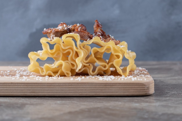 Carne su sfoglie di lasagne sul tagliere, sul piano di marmo.