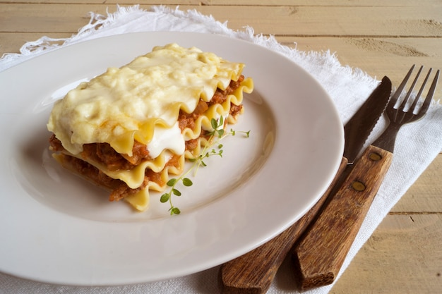 Meat lasagna on a wooden background.