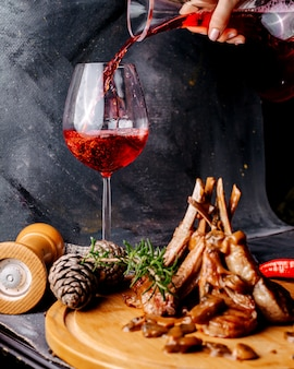 茶色の木製の表面の肉料理と灰色の表面の赤ワイン