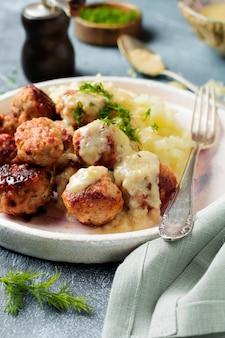 Фрикадельки с картофельным пюре, укропом и сливочным соусом на плотном сером камне или бетоне