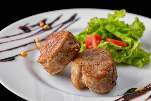 Meat medallions with sauce and greens