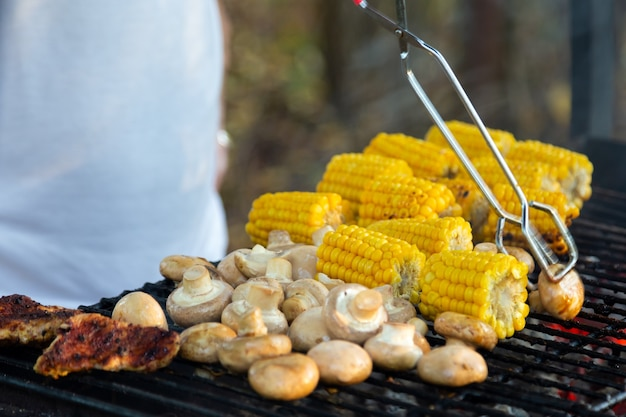 Meat mushrooms corn grilled corn outdoor barbecue hand holding meat tongs