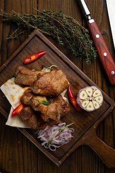 木製のテーブルにニンニクとピタパンの肉