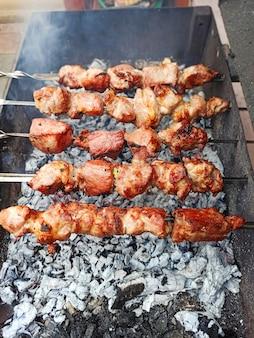 꼬치 고기는 나무, 길거리, 그릴, 피크닉에서 요리했습니다. 뜨거운 석탄의 배경에 돼지 고기.