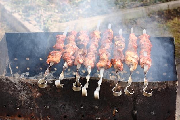 Мясо на шпажках обжаривается на открытом огне в мангале.