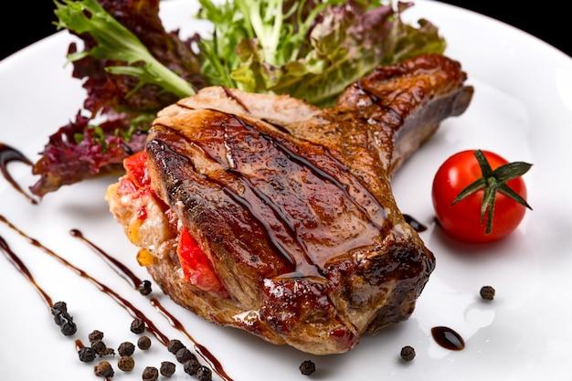 Мясо на кости с овощами на белой тарелке