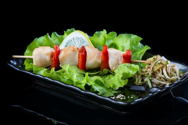 Мясо на деревянных шпажках, свинина, курица, рыба, морские гребешки, говядина, креветки в черной тарелке на черной стене.