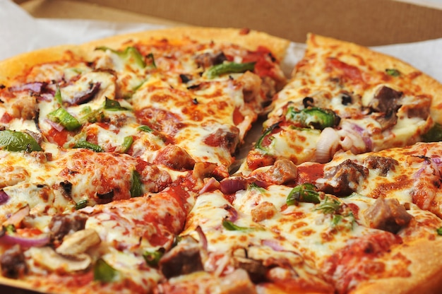 Meat and pepper pizza lies on cardboard