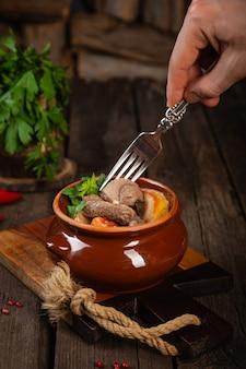 Кусочки мяса в горшочке с соусом, овощами, деревянный фон