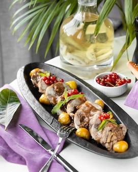 Pezzi di carne con sottaceti e frutti di bosco