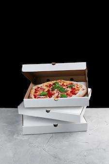 Мясная пицца внутри коробки. стек коробок для пиццы, стоящих на бетонном столе.