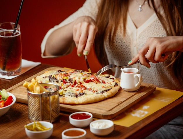 Meat pizza with cheese and vegetables on wooden board