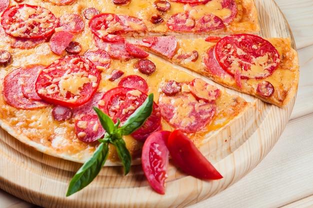 木製のテーブルにトマトと肉のピザ