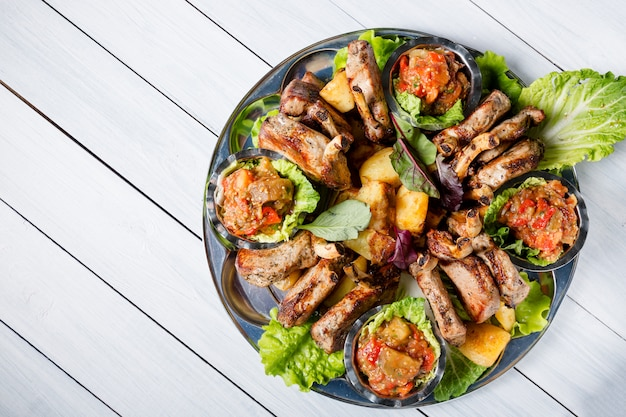 Meat plate with delicious pieces of meat, salad, lamb ribs, grilled vegetables, potatoes and sauce