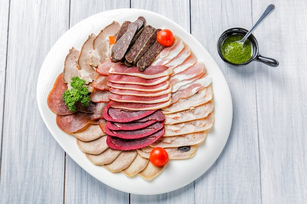 Meat plate with delicious pieces of sliced ham, cherry tomatoes, herbs, meat and sauce