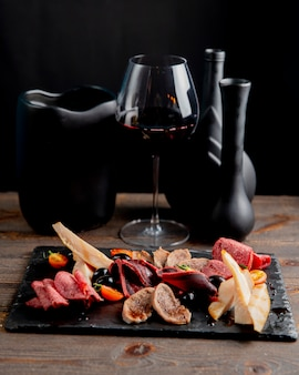 Meat plate with olives and tomatoes served with glass of wine