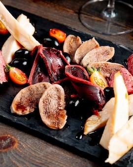 Piatto di carne con olive e pomodori
