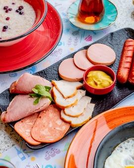 Мясная тарелка с колбасками и соусом