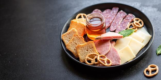肉の盛り合わせ、ハムのスライス、チーズプレート、クラッカーソーセージの燻製または乾燥硬化サラミ