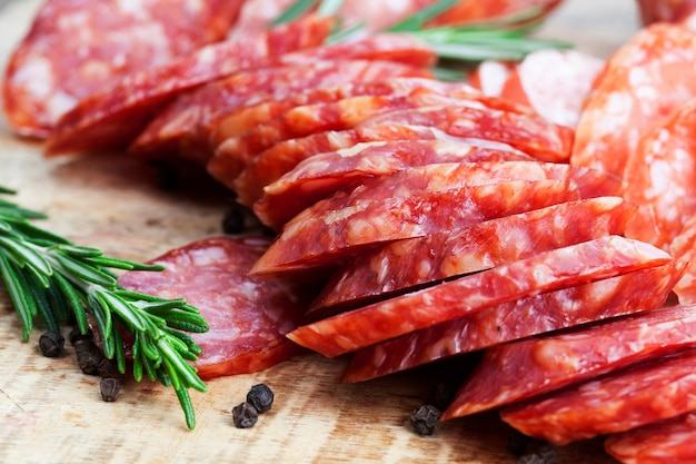 Meat prepared marinated beef, pork products with lard sliced on the table with rosemary