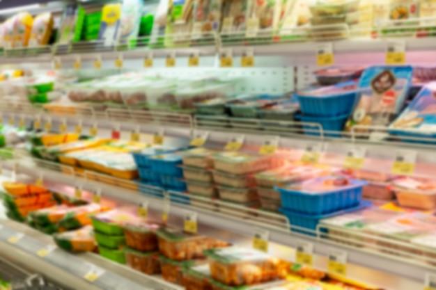 Мясные продукты на полках в магазине. вид сбоку. размытый.