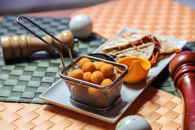 肉のケサディーヤチーズ豆トマトサワークリームポテトボールの側面図
