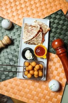 Quesadilla di carne con formaggio, fagioli, salsa di pomodoro e polpette di patate